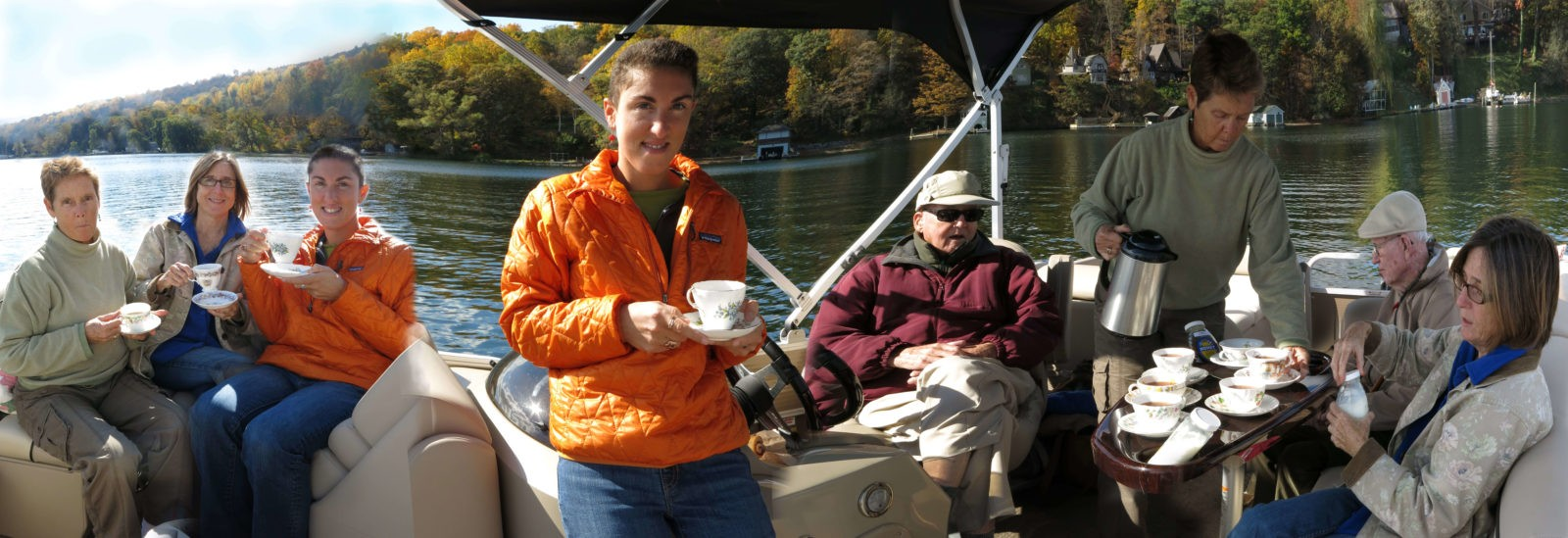 friends with fathers drink tea on a boat on Cayuga Lake in october