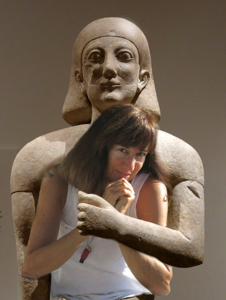Robin Botie being hugged at the Metropolitan Museum of Art by an ancient statue from Mesopotamia or Sumeria or -