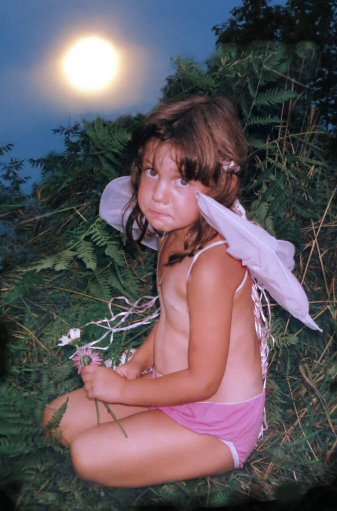 early photo of Marika Warden with angel wings taken by Robin botie of Ithaca, New York at the old Michigan Wymyn's Music Festival