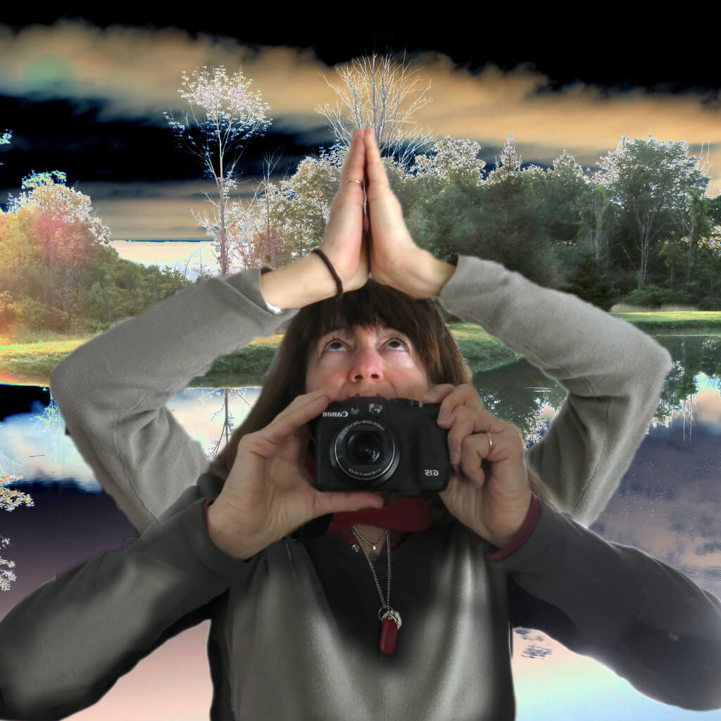 Robin Botie of Ithaca, New York, is reflected, praying with camera