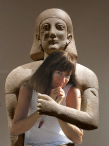 Robin Botie being hugged at the Metropolitan Museum of Art by a statue from Mesopotamia or Sumeria or -